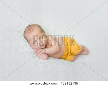 sweet sleeping newborn boy in yellow panties with head on his hand