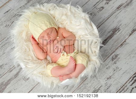 sweet newborn baby in hat and panties sleeping on round bed, top view