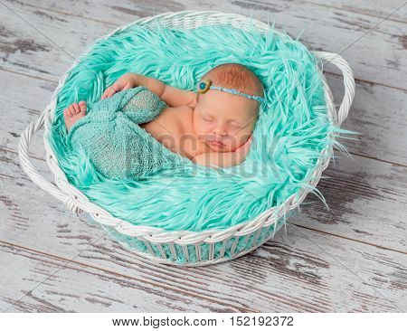 lovely sleeping newborn girl in round cot with turquoise fluffy blanket