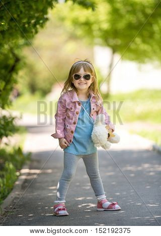 trendy little girl in park with teddybear in hand with sunglasses