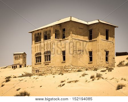 Ghost buildings of old diamond mining town Kolmanskop near Luderitz in Namibia. Abandoned house ruins sunken in the sand dunes of Namib Desert. Vintage toning photography.