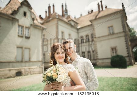 Happy wedding couple hugging and smiling each other on background old castle.