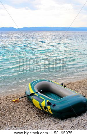 Inflatable blue boat with peddles on pebble beach on summer day on beautiful seascape