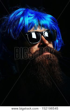 Handsome man hipster fashion model with long brunette beard with moustache in sunglasses and blue wig on black background