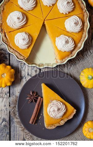 Thanksgiving homemade pumpkin pie with whipped cream and spices on rustic background, top view. Autumn Decoration and rustic style.