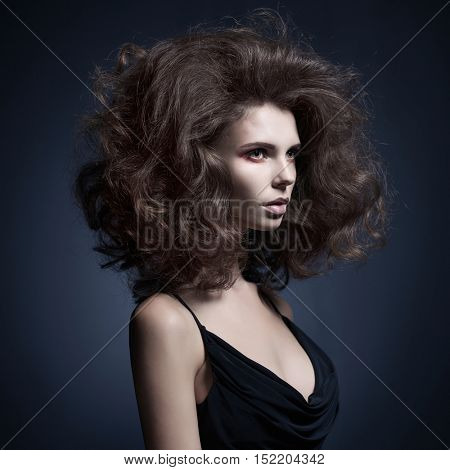 Studio fashion portrait of beautiful woman with volume wavy hair. Big hair