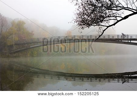 Autumn landscape with river in mist. Cyclist rides through beautiful bridge in strong haze. Fallen leaves on water