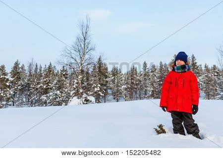 Cute boy in a red parka down jacket outdoors on beautiful winter snowy day