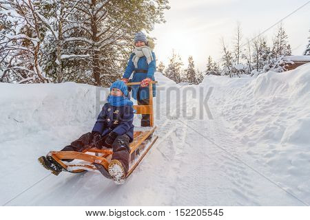 Beautiful family of mother and daughter enjoying snowy winter day outdoors having fun sledging
