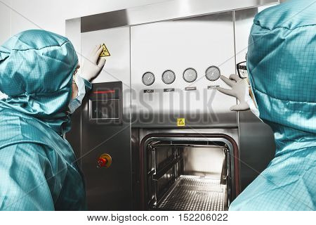 Two scientists works in laboratory and looks at dashboard