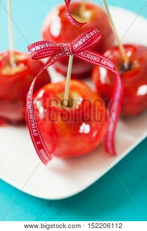 Homemade candied apples with a red bow on a wooden background closeup