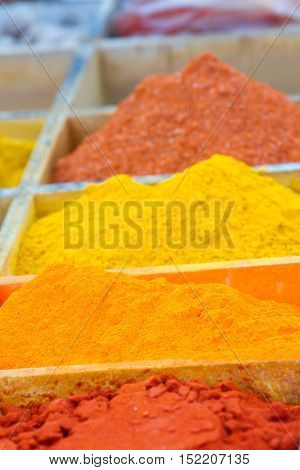 Spice market with colorful seasoning in wooden boxes. Dried herbs
