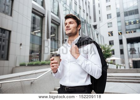 Handsome young businessman with jacket and cup of coffee walking near business center