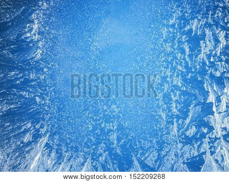 Frosty patterns on the edge of a frozen window. Christmas background.