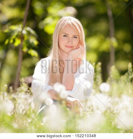 Cute woman rest in the park with dandelions.  Beauty nature scene with outdoor lifestyle. Happy woman sitting on the grass. Happiness and harmony in life.