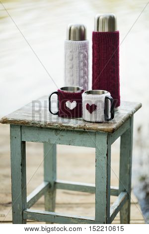 Rustic style. On the old stool is a thermos with cups in knitted covers in white and Burgundy with pattern heart.