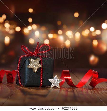 Christmas still life with a gift in front of a festively lit background with bokeh