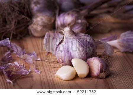 Health garlic on wooden background - whole garlic bulb and sliced garlic