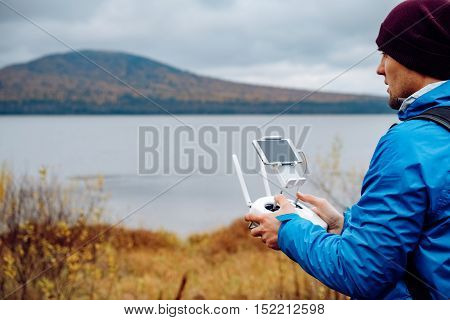 Man with drone flying at the outdoor. Man playing with drone