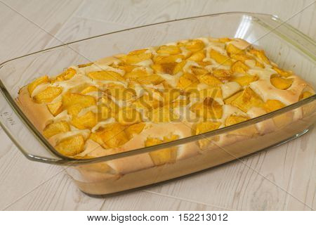 Sweet pie with peach in glass brazier on wood table.