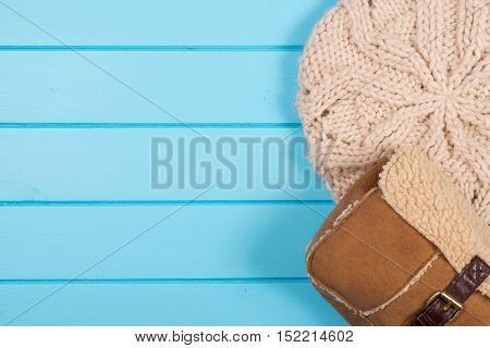Set of womens knitted beret and winter bag on the wooden background.