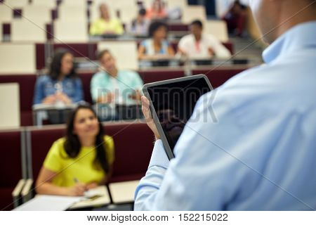 education, high school, university, learning and people concept - close up of teacher with tablet pc computer and students at lecture hall
