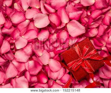 Romantic red rose petals with gift box background