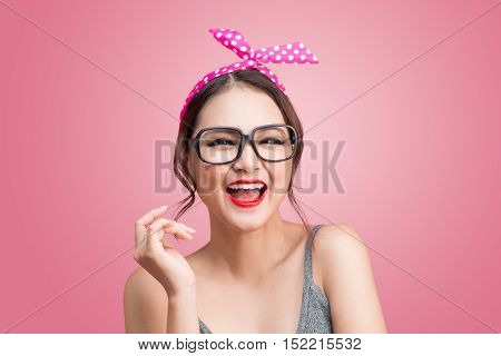 Fashion portrait of asian girl with sunglass standing on pink background.