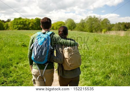 travel, hiking, backpacking, tourism and people concept - happy couple with backpacks hugging and walking along country road