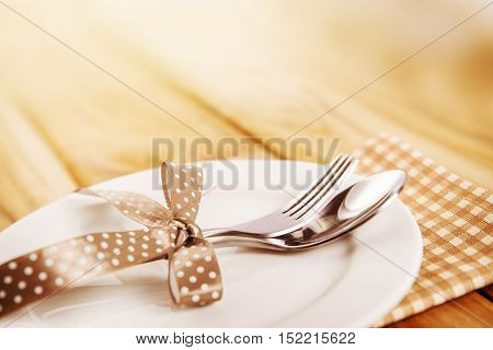 close up dinner setting fork and spoon on plate on wooden background
