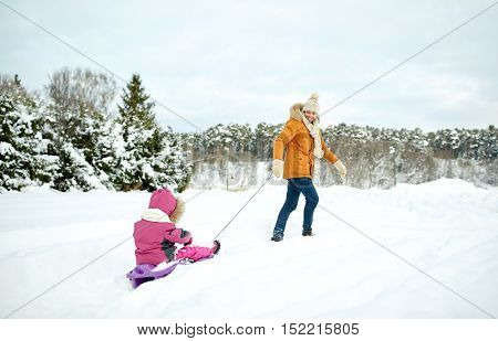 family, sledding, season and people concept - happy father pulling sled with child outdoors in winter