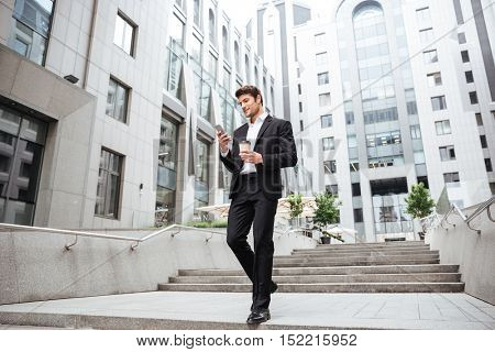 Smiling young businessman using cell phone and drinking coffee in the city