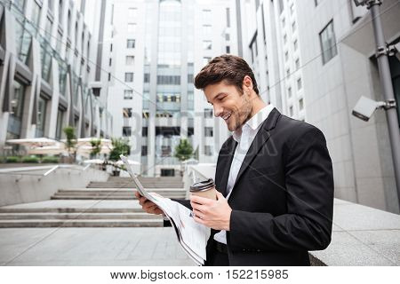 Cheerful young businessman reading newspaper and drinking coffee near business center
