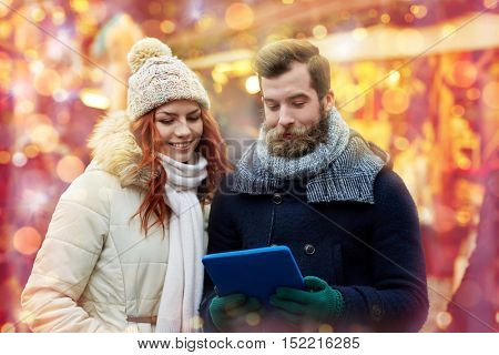 holidays, winter, christmas, technology and people concept - happy couple of tourists in warm clothes with tablet pc computer walking in old town