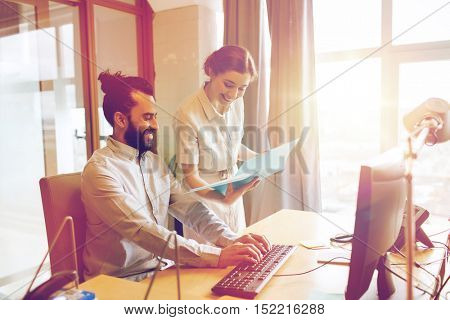 business, startup and people concept - happy creative team with computer and folder in office