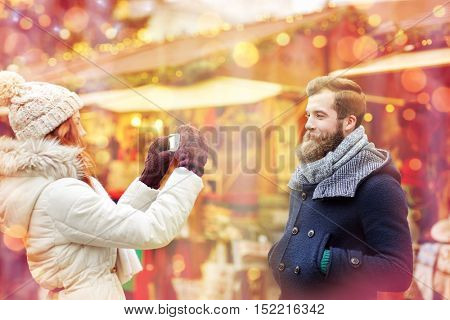 holidays, winter, christmas, technology and people concept - happy couple of tourists in warm clothes taking picture by smartphone or camera in old town