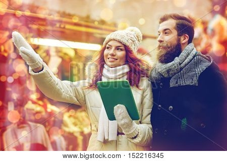 holidays, winter, christmas, technology and people concept - happy couple of tourists in warm clothes with tablet pc computer pointing finger in old town