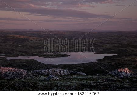 Evening lilac sky over the mountain valleys and lakes. Arctic summer the tundra Norway.