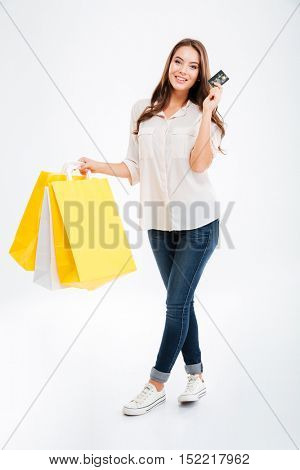 Full length portrait of a happy young woman holding shopping bags and bank card isolated on a white background