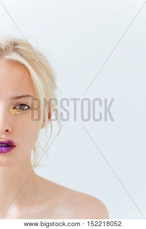 Half face of beautiful young woman with purple stylish makeup over white background