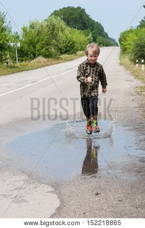 Boy jumping in puddles on the country road