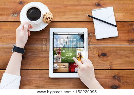 business, technology, mass media and people concept - close up of woman with news on tablet pc computer screen, notebook and coffee on wooden table