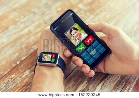 business, technology and people concept - close up of male hand holding smart phone and wearing smart watch with incoming call interface on screen
