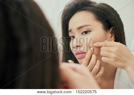 Young woman popping pimple on her check