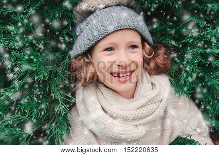 close up winter portrait of happy child girl wearing warm knitted hat and scarf with Christmas tree on background