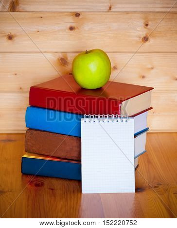 Books notepad and green apple on wooden table over wooden background