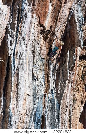 Female Climber ascending natural High Rock making elegant Move Summer style sportive Clothing High Contrast red and blue Stone Texture