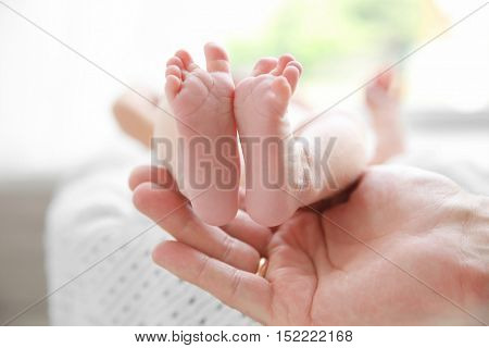 Female hand holding feet of newborn baby girl lying on soft blanket