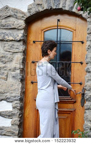 Young female opening external door, back view woman portrait