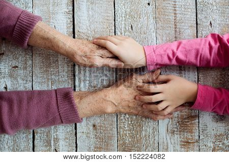 Close up. Unrecognizable grandmother and her granddaughter holding hands. Studio shot on white wooden background.